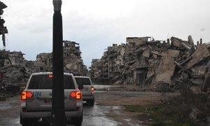 Un convoi de l'UNICEF passe devant des bâtiments détruits à Homs, en Syrie.