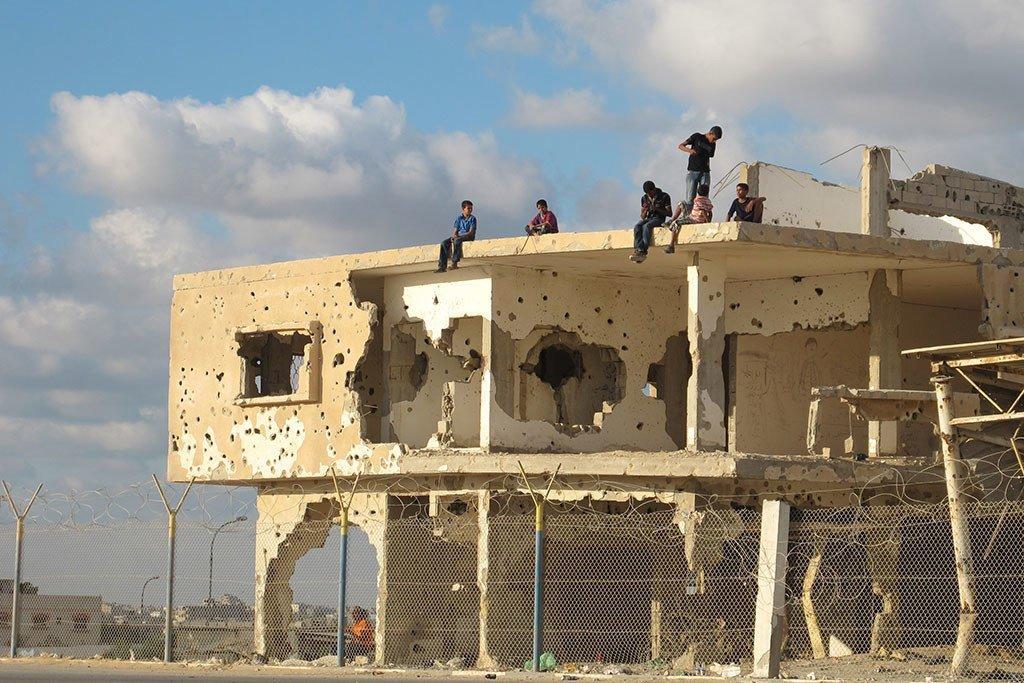 年轻人坐在加沙一个废弃的建筑物上。UN Photo/Shareef Sarhan