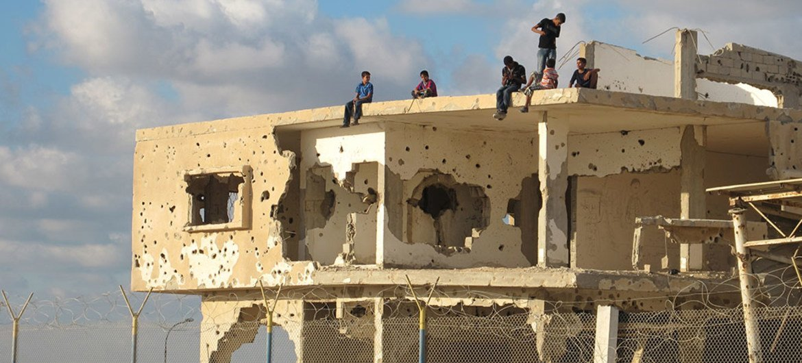 A group of youngsters sit on an abandoned building in Gaza.