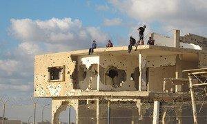 Un groupe de jeunes assis sur un bâtiment abandonné à Gaza.