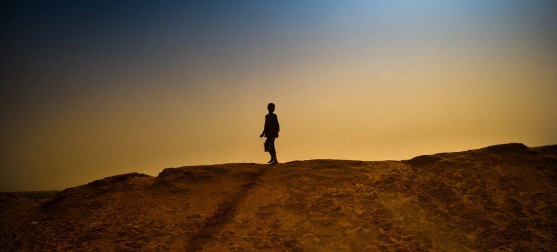 Un garçon marchant sur une dune de sable a proximité du camp de réfugiés de M'bera, en Mauritanie.