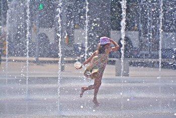 Una niña juega en unas fuentes para aliviar el calor del verano.