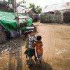 Des enfants marchent entre les abris d'un camp de personnes déplacées dans l'État de Rakhine, au Myanmar, le 6 avril 2017. La plupart des personnes déplacées sont des femmes et des enfants.