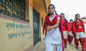 """A 16-year-old girl advocate against child marriage walks to school, passing the words """"Now is not the time to get married, never marry before the age of 18,"""" in her village in Giridih, Jharkhand state, India. (file)"""