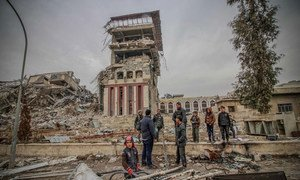 Civilians foraging near the Mosul University Presidency building, which bears the scars of fighting between Iraqi troops and ISIL militants.