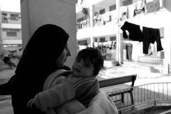 فلسطين،26 عاما، تحمل طفلها. هي أم تعيل وحدها سبعة أطفال. كانت حاملا في شهرها الثامن عندما تم تدمير منزلها وفرت حافية القدمين مع أسرتها الفتية إلى مركز الأونروا في تموز / يوليو 2015. الصورة: صورة الأمم المتحدة / الأونروا / شريف سرحان