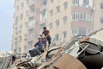 Palestinos recoben sus pertenencias entre los escombros de una torre residencial destruida durante un bombardeo israelí el 24 de agosto de 2014.