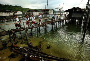 Children cross a bridge as they make their way to school in a remote part of the Sulawesi province, Indonesia.