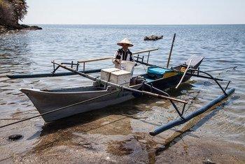 Рыбак выгружает свою традиционную рыбацкую лодку на севере Сулавеси, Индонезия.