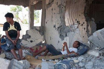 Una familia yemení en su casa, destrozada por combates.