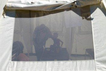 Une jeune fille est aidée à faire ses besoins dans un seau dans un centre de traitement du choléra en Haïti.