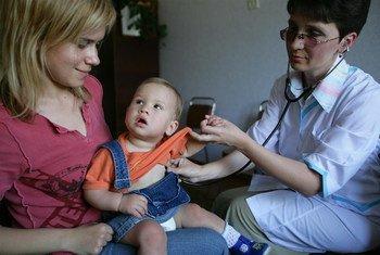 Годовалая девочка на руках у мамы   на приеме у врача. Украина в числе  8 государств, где   в прошлом   году уровень  иммунизации от опасных заболеваний был  ниже  50 процентов. Фото ЮНИСЕФ