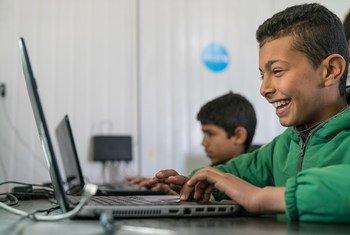 11-летний мальчик из Сирии не может скрыть свою радость, работая на компьютере в учебном центре, организованном ЮНИСЕФ в лагере для беженцев в Иордании