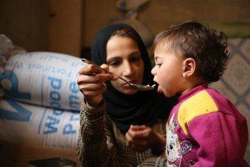 Una madre desplazada de la ciudad de Damasco en Siria, alimenta a su pequeña de un año en un campamento. Foto: PMA/Abeer Etefa