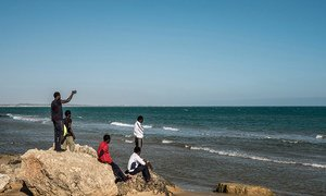 A group of Gambian boys survey the ocean from the beach during an outing from a government hot spot–a reception center that doubles as a lodging station for unaccompanied minors in Pozzallo, Sicily, on May 17, 2016.