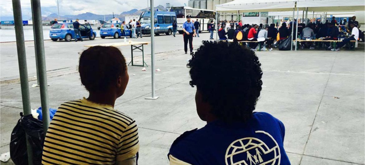 An IOM staff member talks to a migrant at a reception centre.