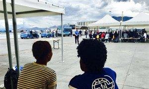 Un membre du personnel de l'Organisation internationale pour les migrations (OIM) parle à un migrant dans un centre d'accueil.