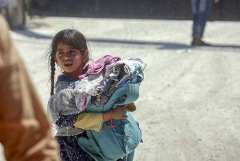 فتاة تحمل حقيبة وملابس مقدمة من اليونيسف بشمال الرقة.UNICEF/Souleiman