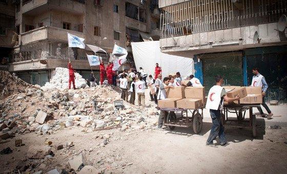 Сотрудники ООН и Красного Полумесяца оказывают помощь жителям восточных районов сирийского Алеппо. Фото УВКБ