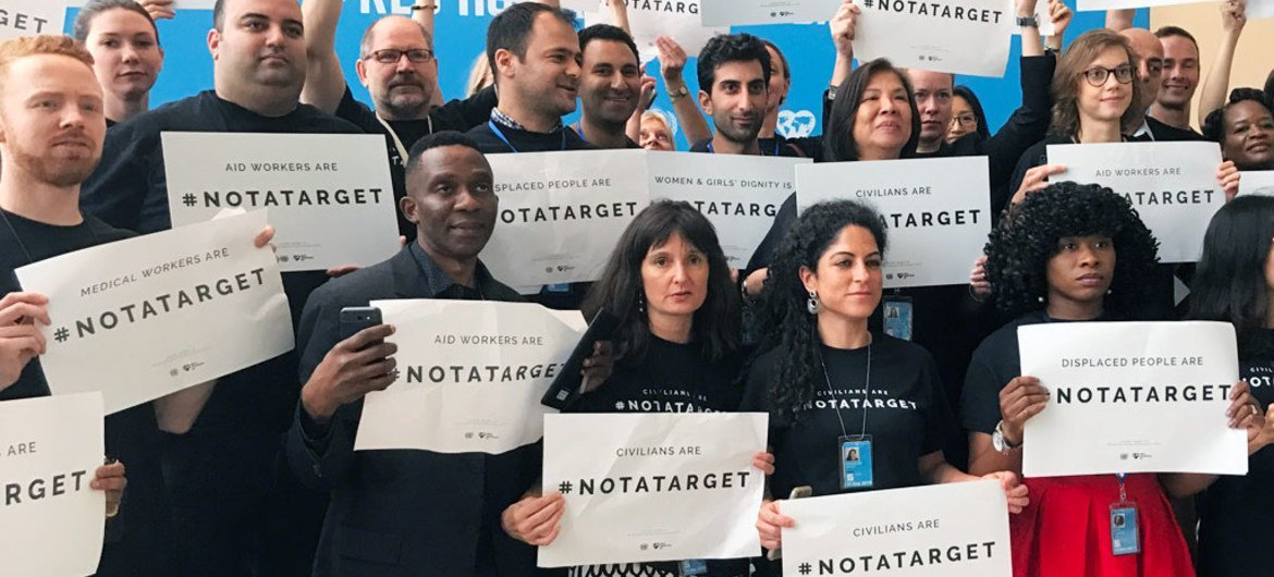 Staff stand together at United Nations Headquarters in New York to draw attention that civilians are <a href=https://twitter.com/hashtag/NotATarget?src=hash>#NotATarget</a>.