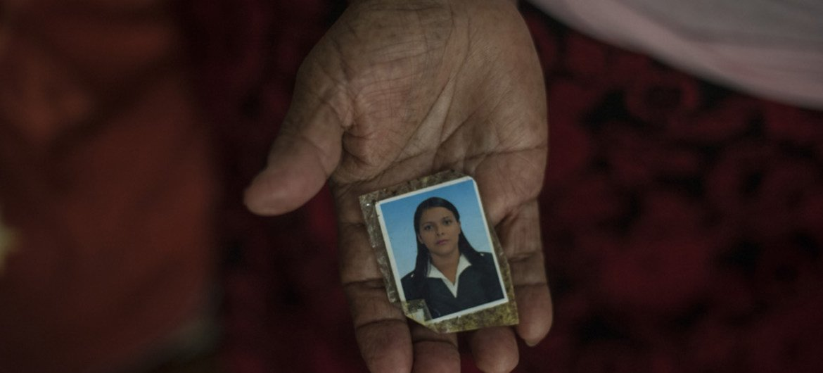 A 71-year-old Salvadorian refugee living in Mexico shows a picture of her daughter, who was murdered by a gang at the age of 27, before the family fled.