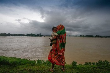 Displaced by the floods, a woman and her child walk along a road in southern Nepal.