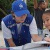 Una trabajadora de la OIM en Honduras informa a esta niña sobre los derechos de los migrantes retornados.