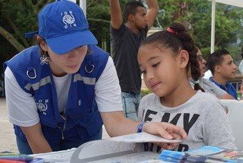 Una trabajadora de la OIM en Honduras informa a esta niña sobre los derechos de los migrantes retornados. Foto: OIM Honduras