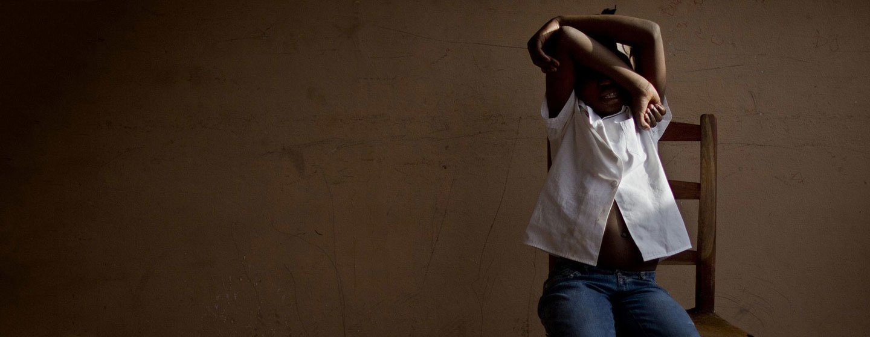 在海地一个联合国儿童基金会支持的中心,一名 8 岁女孩掩面而坐。该中心在当局寻找被贩运儿童的父母时为他们团提供临时照顾和支持。(资料图片)