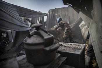 À Kidal, au nord du Mali, un Casque bleu cherche des morceaux de d'artillerie dans un camp de la MINUSMA endommagé par une attaque au mortier intense la nuit du 8 juin 2017. Photo de l'ONU / Sylvain Liechti
