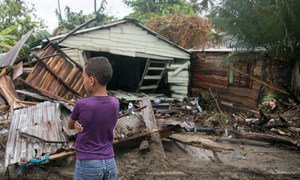 A seven-year old boy stands in front of debris as Hurricane Irma moves off from the northern coast of the Dominican Republic.
