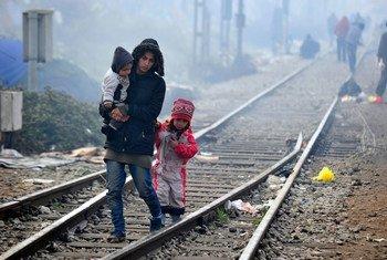 Une femme marche avec ses enfants le long d'une voie ferrée reliant la Grèce et l'ex-République yougoslave de Macédoine en mars 2016 (archives).