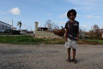 Un enfant de cinq ans devant des bâtiments partiellement détruits sur l'île d'Anguilla qui a été durement touchée par l'ouragan Irma. Septembre 2017.