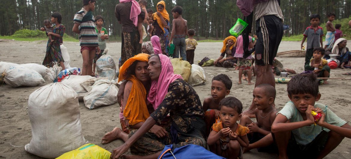 Newly arrived Rohingya refugees sit at Shamlapur beach in Cox's Bazar district, Bangladesh, after traveling for five hours in a boat across the open waters of the Bay of Bengal.
