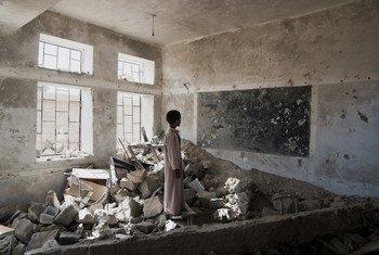 Estudante observa ruínas de sala de aula em escola destruída no Iêmen. Agora, os estudantes frequentam as aulas em uma tenda do Unicef