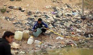 (من الأرشيف) أطفال يملأون أوعيتهم ماء ملوثا - مدينة الطبقة - شمال سوريا