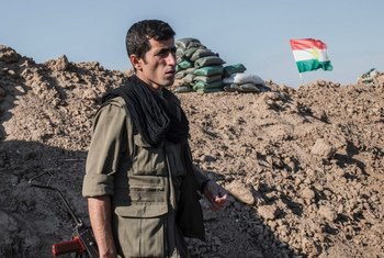 Un combattant kurde dans la province de Kirkouk, dans le nord de l'Iraq. Le drapeau du Kurdistan flotte derrière lui.