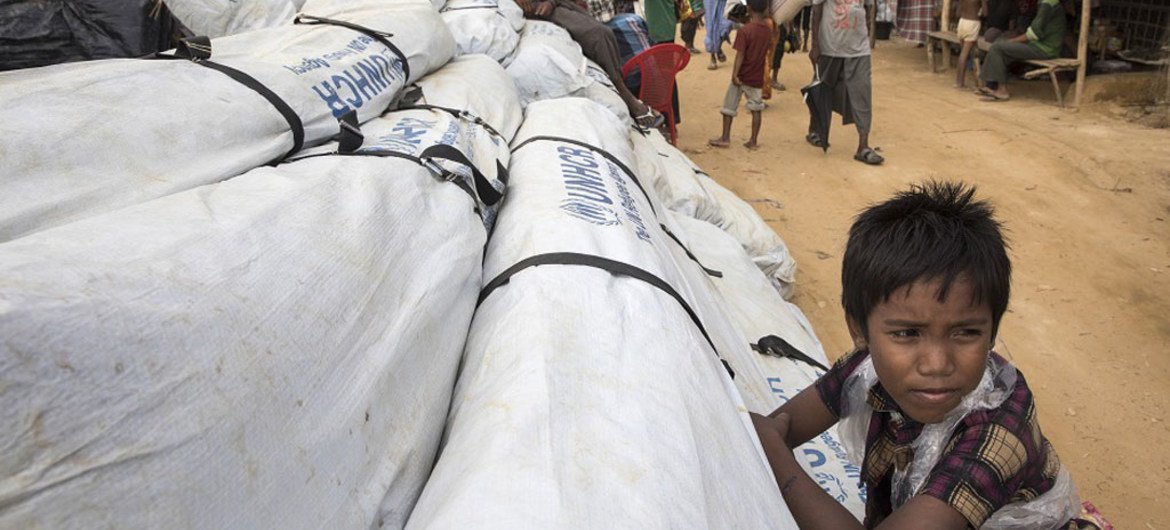 A boy leans against UNHCR tarpaulin, waiting to be distributed at Kutupalong refugee camp.