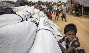 Un garçon s'accroche à de l'assistance du HCR qui doit être distribuée dans le camp de réfugiés de Kutupalong, au Bangladesh. Photo ©UNHCR/Paula Bronstein
