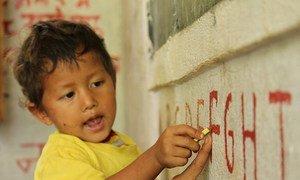 Un jeune garçon indique la lettre F, avec l'aide de son enseignant dans une école rurale au Népal.