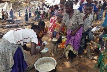 En el centro de tránsito de Nchelenge en Chiengi, en la provincia de Luapula en el norte de Zambia, refugiados congoleses reciben comida proporcionada por las autoridades locales y el ACNUR. Foto: ACNUR / Pumla Rulashe