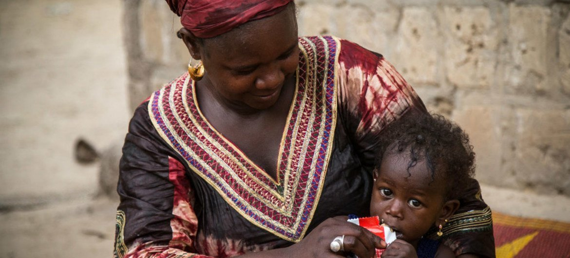 At the Bellafarendi Health Center, Azaharatou Dicko gives UNICEF-supplied ready-to-use therapeutic food to her daughter, Farimata Dicko, 13 months, who suffers from severe acute malnutrition.
