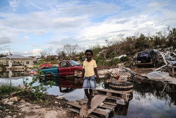 A seven-year-old girl crosses an improvised wooden bridge which she built after Hurricane Irma caused severe damaged in the Five Cays' settlement of Providenciales, in the Turks and Caicos Islands.