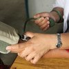 A close-up on hands as skilled health worker takes the blood pressure of a patient. Photo Aisha Faquir/World Bank