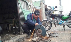 Hassan Hosseini working in a metal workshop that he partially owns, due to assistance from UN migration agency (IOM) offices in Greece and Afghanistan.