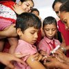 A health worker marks a boy's finger with ink to show that he has been vaccinated against measles in India's Gujarat State.