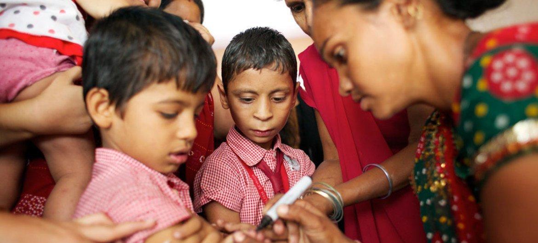 印度古吉拉特邦,一位医护人员正在用墨水给接种过麻疹疫苗的男孩手指上做标记。