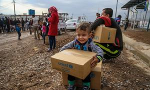 A three-year-old boy sits on a box of winter clothing that his family has received from a distribution at Kawergosk Syrian Refugee Camp in Erbil Governorate in the Kurdistan region of Iraq.