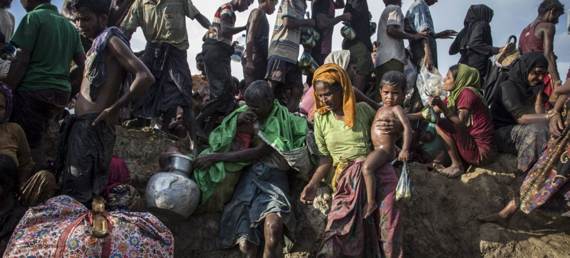 Pictured here, Rohingya refugees including women and children cross from Myanmar into Bangladesh at Palong Khali in Cox's Bazar district.