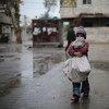 Una niña carga leña para su familia en la ciudad asediada de Ghouta oriental, en Siria. Foto: UNICEF / Al Shami